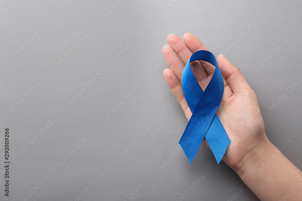 Fototapeta Woman holding blue awareness ribbon on grey background, top view with space for text. Symbol of social and medical issues