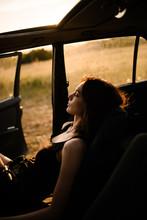 A Woman Enjoying The Sun In Her Car.