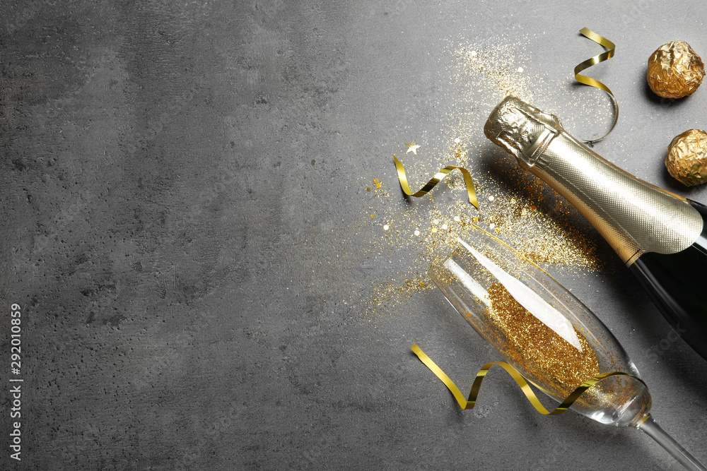Fototapeta Flat lay composition with bottle of champagne for celebration on grey stone background. Space for text