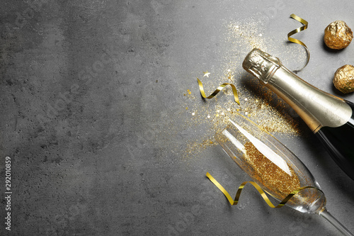 Fotografía  Flat lay composition with bottle of champagne for celebration on grey stone background