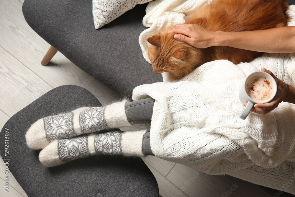 Fototapeta Woman with cute red cat and coffee on grey sofa at home, top view