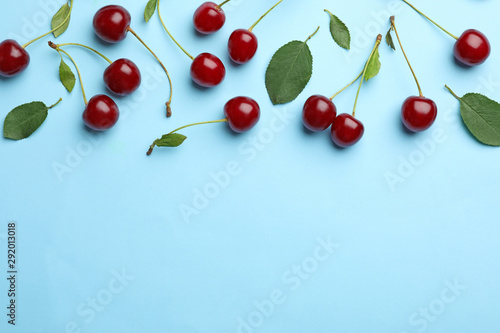 Tasty ripe cherries with leaves on light blue background, flat lay Fototapete