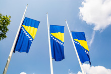 Three Bosnian Flags In Wind On Blue Sky With Clouds