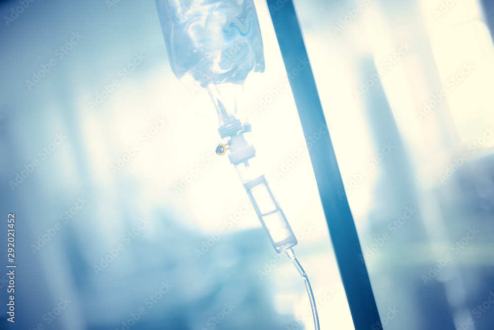 Fototapeta Intravenous drip in the pole against the bright light.