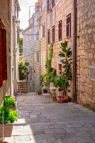 Poster Scooter Narrow stone street with stone houses and facades and flowers in historic fortified Korcula town, Korcula Island, Dalmatia, Croatia