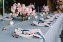Stylish And Beautiful Wedding Table Service With Blue Tablecloth, Festive Dishes And Gentle Pink Napkins
