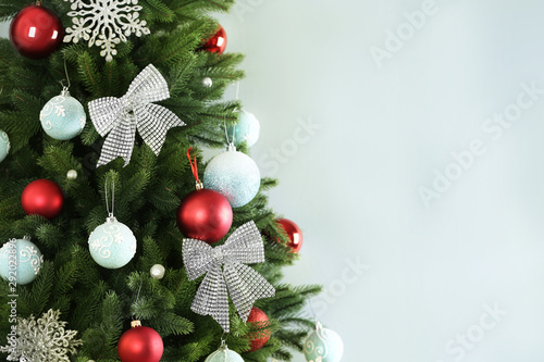 Poster Trees Beautiful Christmas tree with decor against light grey background. Space for text