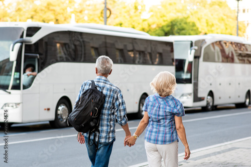 Senior couple of tourists on vacation in front of tourist bus Canvas Print