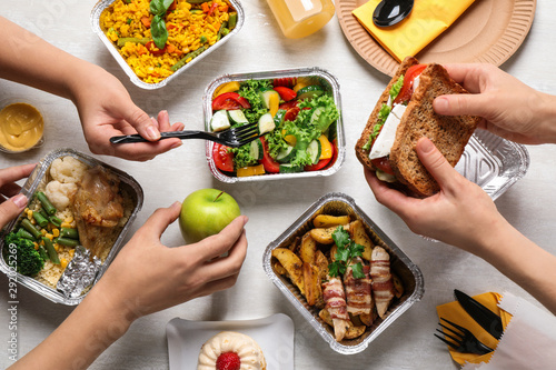 People with lunchboxes at white wooden table, top view. Healthy food delivery - 292025269