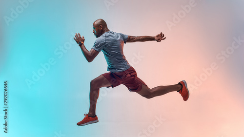 Full length of young african man in sports clothing jumping against colorful background