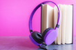 canvas print picture - Open notebook with violet headphones over pink background. Audio book concept