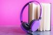 Leinwanddruck Bild - Open notebook with violet headphones over pink background. Audio book concept