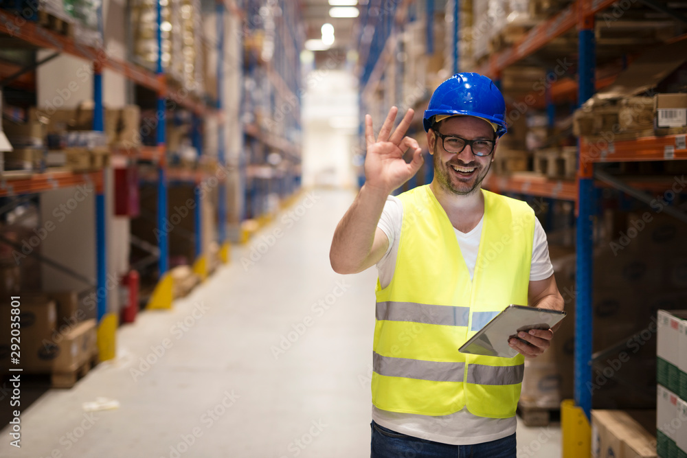 Fototapeta Successful goods distribution and warehouse organization. Warehouse worker standing in large storage center and showing OK hand gesture satisfied on delivering goods.