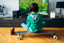 Kid Playing With A Video Game Console At Home Sitting On The Skateboard