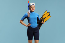 Woman In A Snorkeling Suit Holding Fins And Wearing A Diving Mask