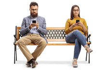 Bearded Man And A Young Woman Sitting On A Bench And Using Mobile Phones
