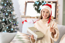 Beautiful Young Woman With Christmas Gift Showing Thumb-up At Home