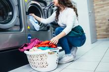 Beautiful Female Employee Working At Laundromat Shop.