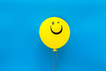 Happiness Emotion. Yellow Balloon With Smile On Blue Background Top View Copy Space