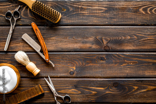 Barbershop concept. Hairdressing tools on dark wooden background top view space for text