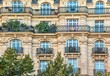 canvas print picture - Street view of an old, elegant residential building facade in Paris, with ornate details in the stone walls, french doors and wrought iron railings on the balconies.