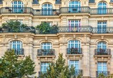 Fototapeta Fototapety Paryż - Street view of an old, elegant residential building facade in Paris, with ornate details in the stone walls, french doors and wrought iron railings on the balconies.