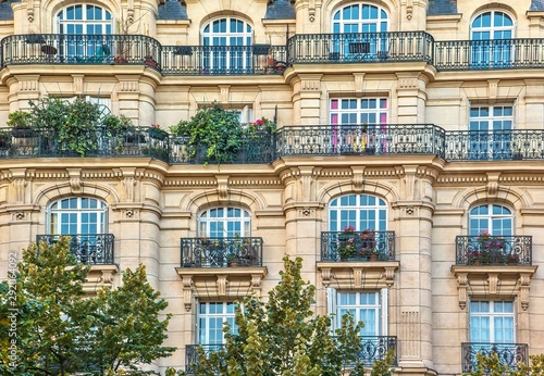 Street view of an old, elegant residential building facade in Paris, with ornate details in the stone walls, french doors and wrought iron railings on the balconies. - 292064092