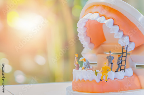 Photo Miniature worker people or small figure cleaning white tooth model as medical and healthcare concept