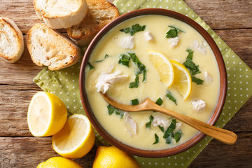 Thick aromatic Greek lemon soup with chicken and orzo paste close-up in a bowl. Horizontal top view