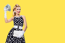 Portrait Of Beautiful Young Happy Excited Girl With Money Cash, In Pinup Style Black Dress With White Polka Dot, Over Yellow