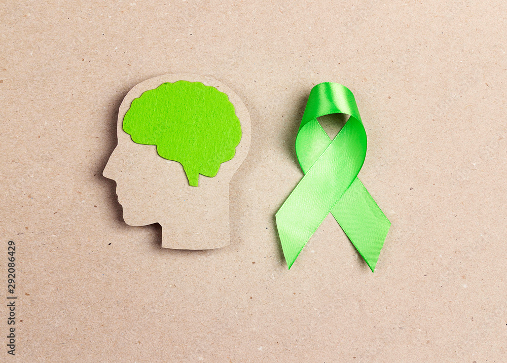 Fototapeta World mental health day concept. Green awareness ribbon and brain symbol.