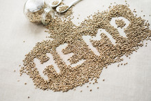 Word HEMP Made Of Hemp Seeds On Linen Background. Healthy Eating Supplement. Superfood Concept. Top View.