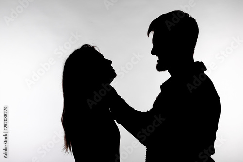 Photo Domestic violence and abuse concept - Silhouette of a man asphyxiating a woman