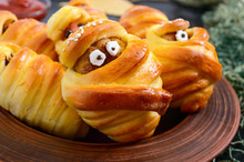 Funny Sausage And Cutlets Mummies In Dough With Eyes, Ketchup On Table. Halloween Food. Close Up