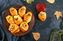 Funny Sausage And Cutlets Mummies In Dough With Eyes, Ketchup On Table. Halloween Food. Top View. Flat Lay