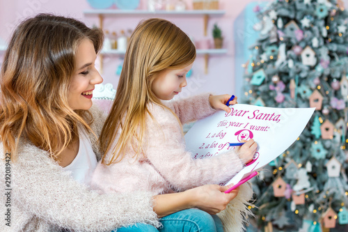 Pinturas sobre lienzo  Smiling woman and little girl child spend time together in light christmas kitchen
