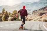 Man skateboarding at mountain road