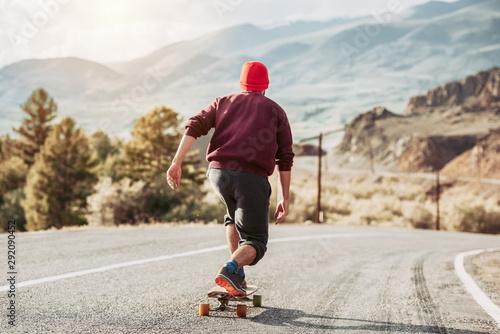 Man skateboarding at mountain road