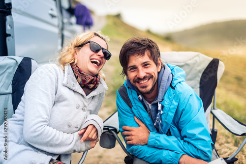 Young couple smiling with  motorhome, RV or campervan on beach. Fototapeta