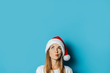 Young Woman In Santa Claus Hat With A Mysterious Face On A Blue Background. Concept Idea For New Year And Christmas