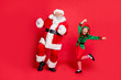 Leinwanddruck Bild - Full body photo of excited two santa claus in hat headwear dancing on festive event wearing green bright costume isolated over red background
