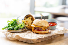 Cheeseburger With Lettuce, Tomato, Fries, And Melted Cheese. The Table In The Restaurant. Unhealthy Food.