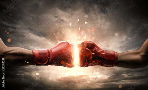 Fotografia Boxing fight, close up of two fists hitting each other over dark, dramatic sky w