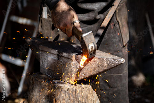 The blacksmith manually forging the molten metal on the anvil in smithy with spa Poster Mural XXL