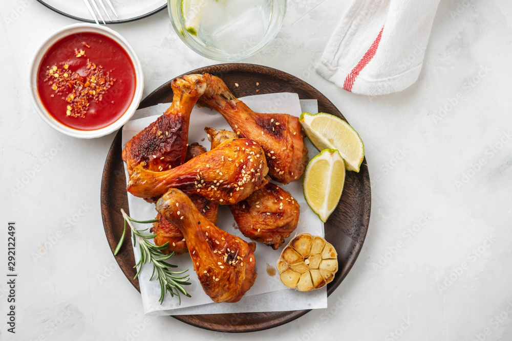 Fototapety, obrazy: Chicken legs with sauce, rosemary and lime on a white background. Copy space. Top view.
