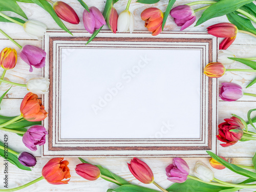 Colorful tulips around wooden frame in spring sunlights. - 292122429