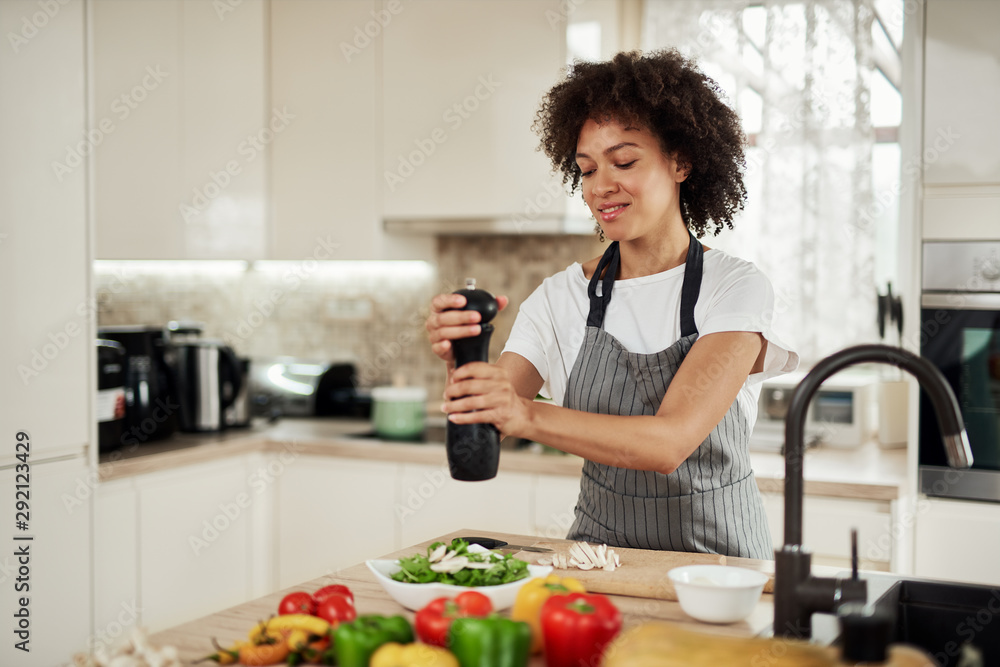 Fototapeta Attractive mixed race woman in gray apron addinf pepper in bowl with rocket and mushrooms. On kitchen counter are different vegetablet.