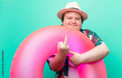 young big size man with a inflatable donut against flat wall Wallpaper Mural