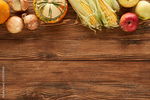 top view of raw sweet corn, onions, pumpkins and apples on brown wooden surface