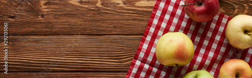 panoramic shot of checkered tablecloth with fresh apples on wooden surface